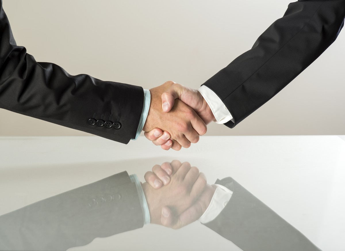 closeup-of-business-people-shaking-hands-over-a-deal